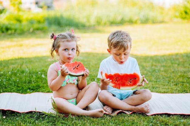 Due bambini mangiano l'anguria in giardino. i bambini mangiano la frutta all'aperto. spuntino sano per i bambini. la ragazza e il ragazzo dei più piccoli si godono l'anguria
