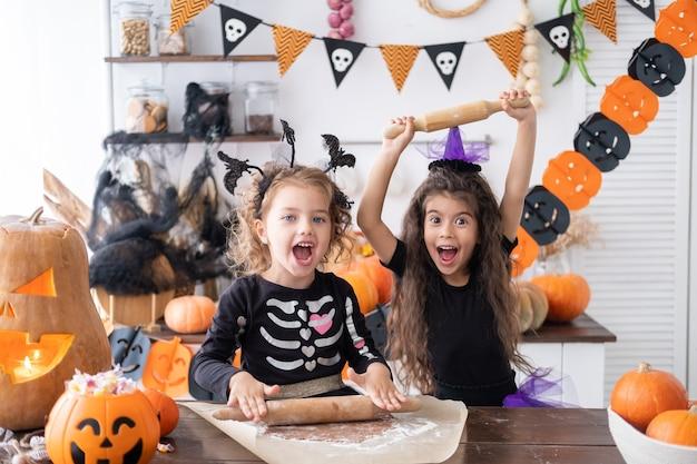 Una ragazza di due bambini in costume da strega, che cuoce i biscotti, si diverte in cucina, festeggia halloween.