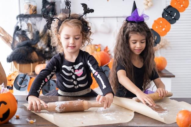 Ragazza di due bambini in costume da strega che cuoce i biscotti che si divertono in cucina a festeggiare halloween
