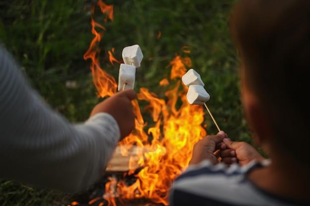 Due mani di bambini si siedono arrostire salsicce al fuoco nella foresta. vicino alla tenda. tempo libero con la famiglia, genitorialità. concetto di famiglia felice