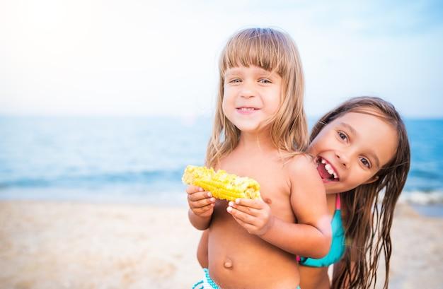 Due bambini che si divertono sulla spiaggia, sorridendo e mangiando mais. ragazze che esaminano macchina fotografica, ritratto su sfondo sfocato