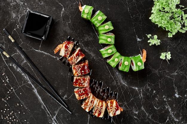 Due tipi di involtini di sushi con gamberi su sfondo nero