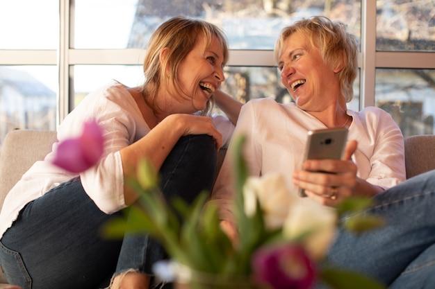 Due signore di 55 anni che ridono allegramente, guardandosi l'un l'altro, concetto di amicizia femminile female