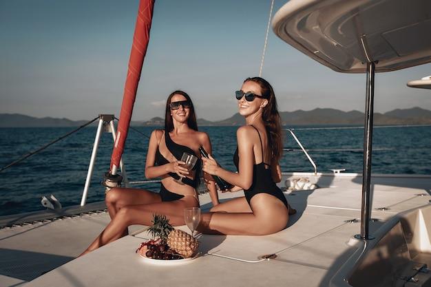 Due signore in costume da bagno nero e occhiali da sole trascorrono felicemente le vacanze estive bevendo champagne sul loro yacht.