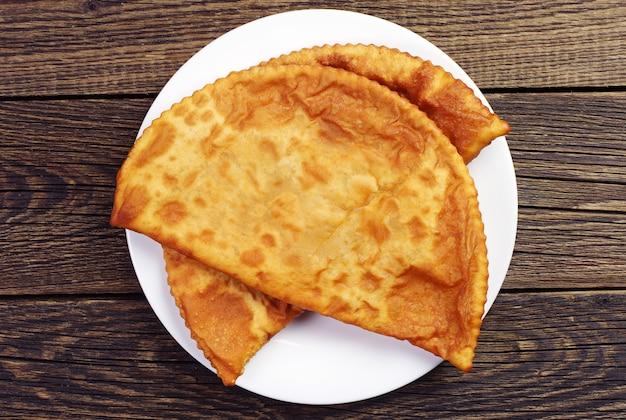 Due grandi pasticcini gustosi in un piatto su fondo di legno