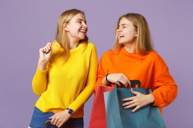 Due sorelle gemelle bionde ridenti in abiti vivaci tengono la carta di credito, il pacchetto con gli acquisti dopo lo shopping isolato sulla parete blu viola. concetto di famiglia di persone.
