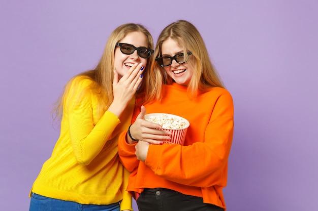 Due giovani sorelle gemelle bionde ridenti in occhiali 3d imax che guardano film, tenendo in mano popcorn isolato su parete blu viola pastello. concetto di stile di vita familiare di persone.