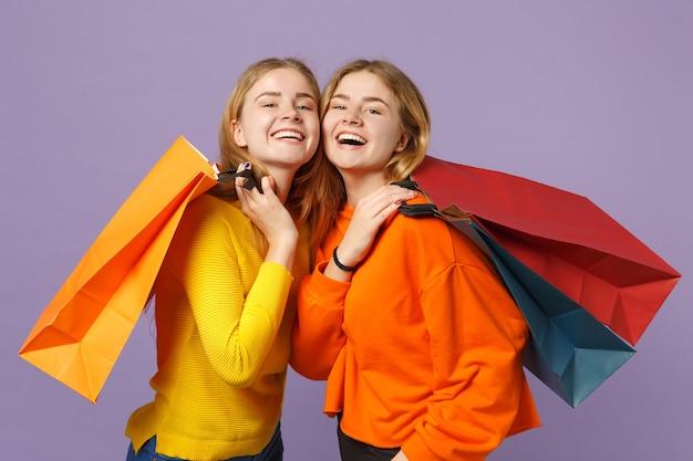 Due giovani sorelle gemelle bionde ridenti in abiti vivaci tengono la borsa del pacchetto con gli acquisti dopo lo shopping isolato sulla parete blu viola. concetto di stile di vita familiare di persone.