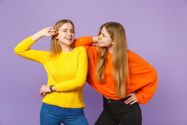 Due giovani sorelle gemelle bionde ridenti in abiti colorati vividi in piedi, da parte isolate sulla parete blu viola pastello. concetto di stile di vita familiare di persone.