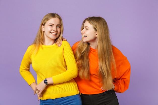 Due giovani sorelle gemelle bionde ridenti in abiti colorati vividi in piedi, guardandosi l'un l'altro isolati sulla parete blu viola pastello. concetto di stile di vita familiare di persone.