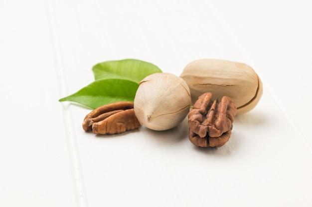 Due foglie, noci pecan sbucciate e non sbucciate su un tavolo di legno bianco