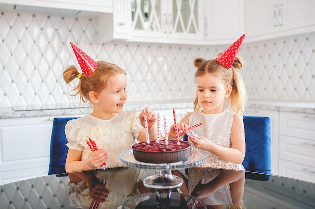 Due bambine bionde di circa cinque anni nella luminosa cucina decorano la torta di compleanno con candele rosse e bianche, compleanno
