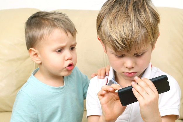 Due ragazzini guardano lo smartphone. le relazioni tra bambini e gadget moderni