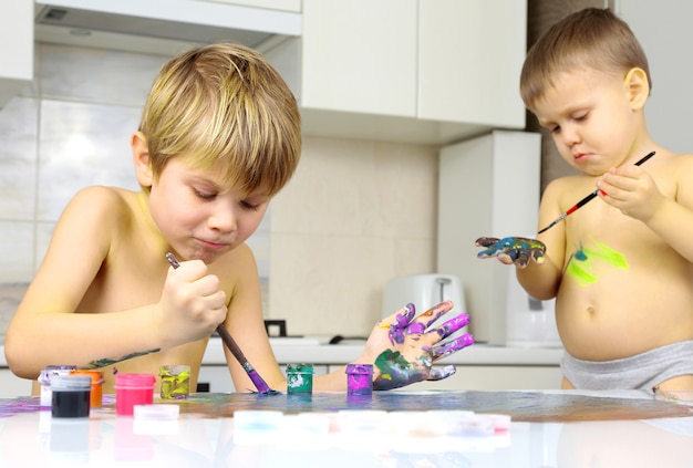 Due ragazzini dipingono su un tavolo bianco. creatività artistica nello sviluppo dei bambini