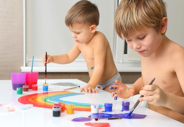Due ragazzini dipingono su un tavolo bianco