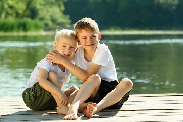 Due ragazzini si siedono in un abbraccio sulle rive del fiume. concetto di amicizia e fratellanza