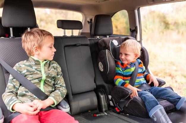 Due ragazzini seduti su un seggiolino per auto e un rialzo si sono allacciati in macchina.