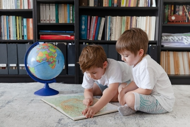 Due ragazzini seduti a casa con il globo ed esplorando la mappa, alla ricerca della prossima destinazione di viaggio