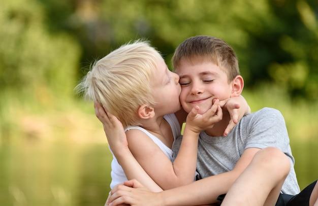 Due fratelli piccoli sono seduti all'aperto. uno bacia l'altro sulla guancia. alberi verdi sfocati in lontananza. concetto di amicizia e fratellanza.
