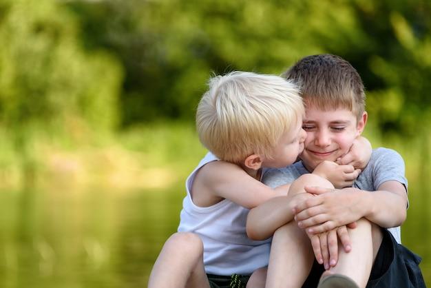 Due fratelli piccoli sono seduti all'aperto. uno bacia l'altra guancia. alberi verdi sfocati in lontananza. amicizia e fratellanza.