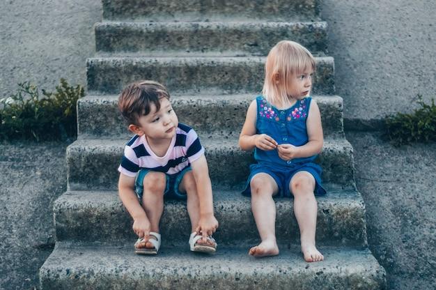 Due piccoli bambino, ragazza e ragazzo in natura, seduti sui gradini di pietra guarda da parte, all'aperto
