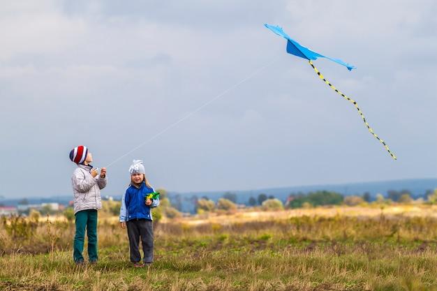 Un ragazzo e una ragazza di due piccoli bambini che giocano fuori con un aquilone