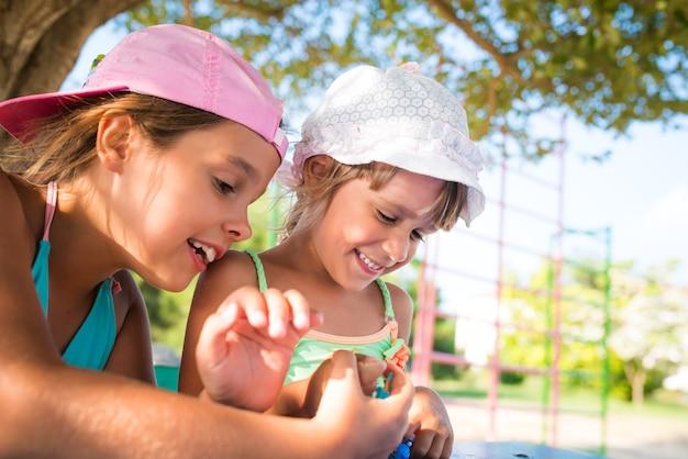 Due bambine carine che giocano a bambole all'aperto mentre si rilassano sulla spiaggia in una calda giornata estiva