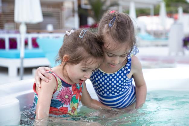 Due sorelline carine giocano in piscina. valori familiari e amicizia.