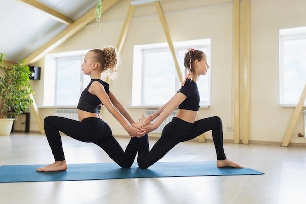 Due bambine in abiti sportivi neri che praticano yoga lavorano insieme su stuoie da palestra in studio