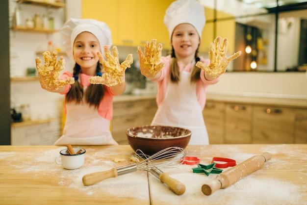 Due bambine cuochi in berretto mostra le mani ricoperte di pasta, la preparazione di biscotti in cucina. i bambini cucinano la pasticceria, i bambini chef fanno la pasta