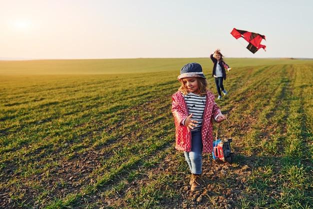 Due amici di bambine si divertono insieme con l'aquilone e l'automobile del giocattolo sul campo al giorno soleggiato