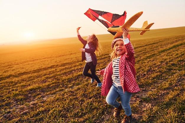 Due amici di bambine si divertono insieme con l'aquilone e l'aereo giocattolo sul campo durante il giorno soleggiato