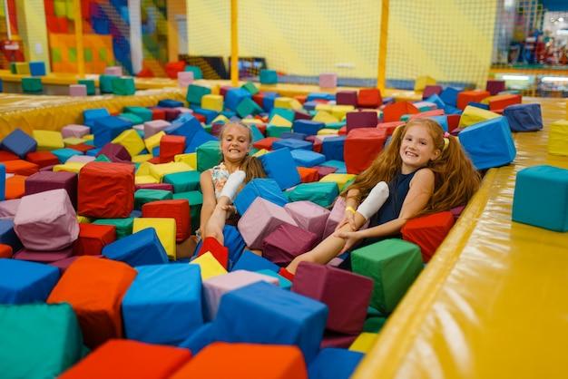 Due bambine che si trovano in cubi morbidi, parco giochi nel centro di intrattenimento. area giochi interna, sala giochi