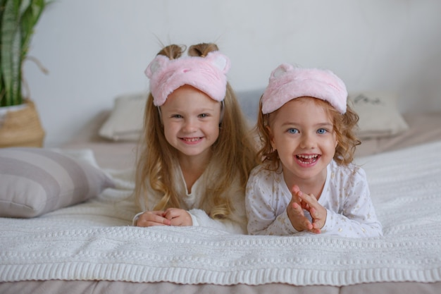 Due bambine in pigiama si siedono sul letto e si sbizzarriscono