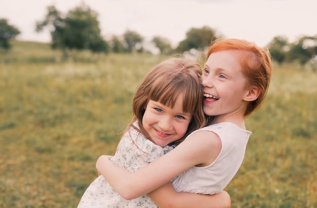 Due sorelle bambine giocano e si divertono sull'erba tenendosi per mano in abiti leggeri.