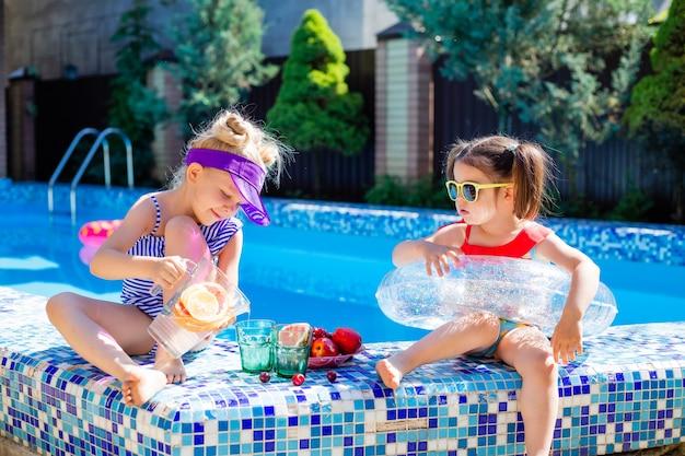 Due bambine si siedono a bordo piscina in estate indossando occhiali da sole e bevendo limonata
