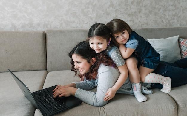 Due bambine si siedono sulla schiena della madre mentre lavorano al computer. lavoro a distanza a casa