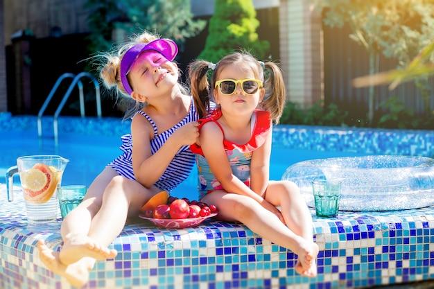 Due bambine che si siedono in costume da bagno a bordo piscina bevendo limonata
