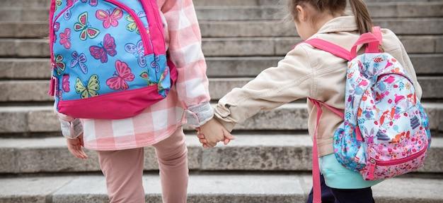 Due bambine con bellissimi zaini sulle spalle vanno a scuola insieme mano nella mano. concetto di amicizia d'infanzia.