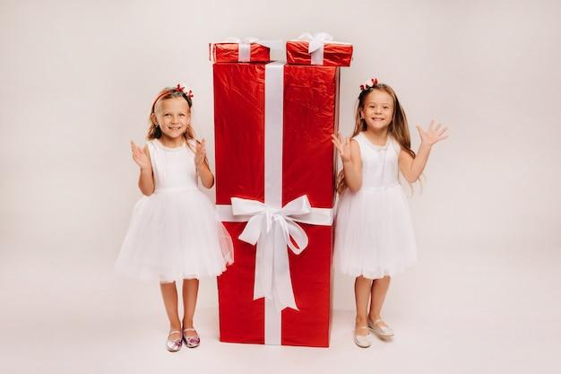 Due bambine con regali di natale su un bianco e un enorme regalo.