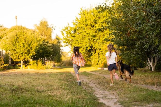 Due bambine con il cane che corre sulla strada
