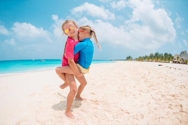 Due bambine felici si divertono molto alla spiaggia tropicale giocando insieme