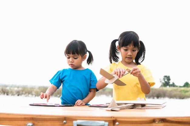 Due bambini piccoli che giocano con un aeroplano giocattolo di cartone nel parco durante il giorno.