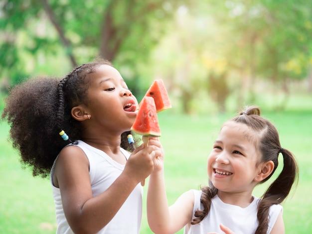 Due bambine adorabili di varie etnie che si divertono a mangiare anguria nel parco.