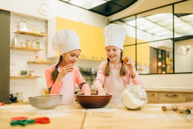 Due sorelline cucinano in berretti, preparano biscotti in cucina. bambini che cucinano pasticceria, chef bambini fanno la pasta, bambino che prepara la torta