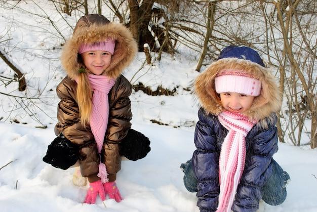 Due sorelline che giocano con la neve all'aperto