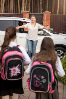 Due sorelline con gli zaini che corrono dalla madre incontrandole dopo le lezioni