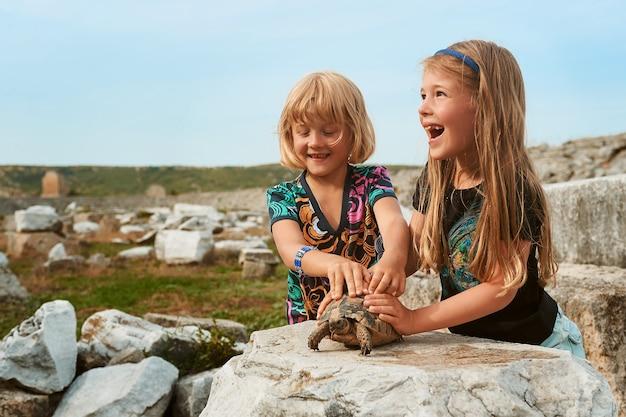 Due bambine sorridenti giocano con la tartaruga