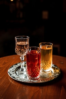 Due cocktail long drink con ghiaccio in bicchieri highball vintage e un bicchiere di vino o vermouth su un vassoio d'argento