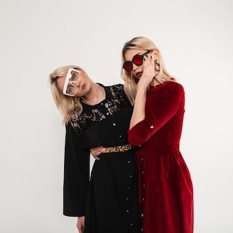 Due belle amiche attraenti in abiti eleganti alla moda in stile retrò in eleganti occhiali belli in posa nella stanza vicino al muro bianco vintage